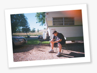 Tom reads No Country for Old Men outside Darryl's RV.