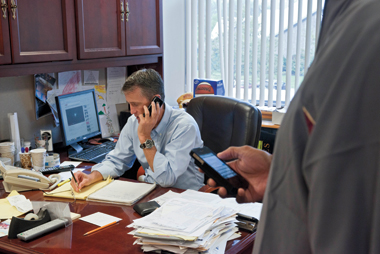 After viewing a recruiting tape in his office, Donahue talks by phone with a high school coach as assistant coach Akbar Waheed checks travel schedules. Photograph: Lee Pellegrini