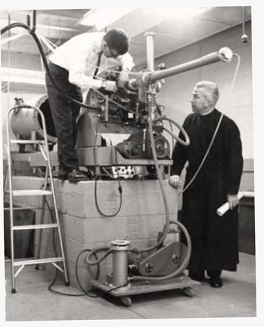 The University's atom-smasher in 1961—and, at right, physics department chair William Guindon, SJ. Photograph: Boston Globe. Click image to enlarge.