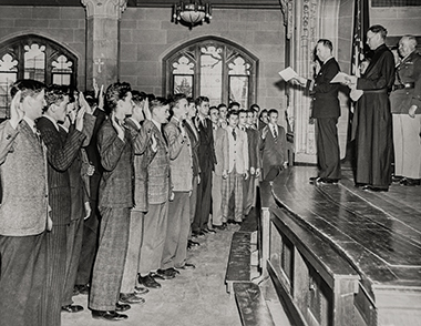 Students are sworn into the Navy in the spring of 1942, in Bapst Library's basement auditorium. At right onstage is University President William J. Murphy, SJ. Photograph: Courtesy of the Office of Marketing Communications. Click image to enlarge.