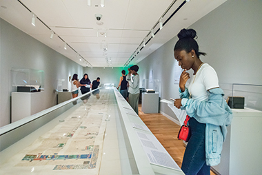 Maame Aba Ewusi Mensah, an exchange student from London, looks at a 34-foot-long, 15th-century French roll that illustrates the history of the world, in the third-floor Monan Gallery.