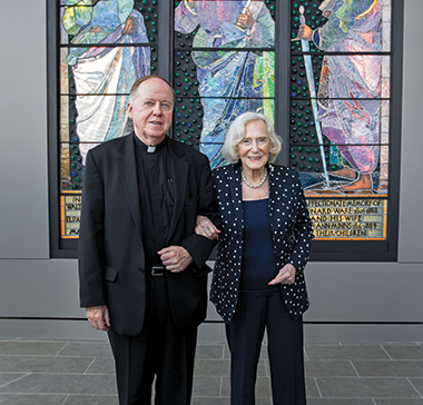 Jacqueline McMullen with University President William P. Leahy, SJ, before the La Farge windows in the museum named for her and her late husband, John. Photograph: Rose Lincoln. Click image to enlarge.
