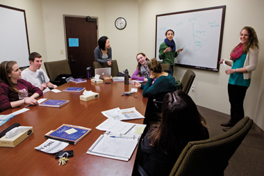 Student coaches (standing, from left) Zhu, Alleyne, and Wostbrock rehearse a presentation. Photograph: Caitlin Cunningham
