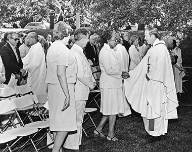 On the lawn alongside St. Mary's Hall on June 3, 1980, at a Mass celebrating his 25th year in the priesthood. Monan greets Mary Latson, a receptionist in his office. Image: Courtesy John J. Burns Library Archive