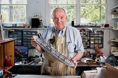 Nolan, in his home studio, with a 25-inch rendering of American Flyer, a 459-foot cargo ship. Image: Peter M. Julian