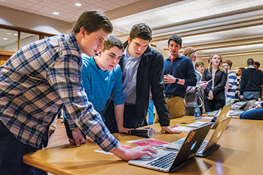 Nick Loeper '18 demonstrates Fisherman, a website development software that he cocreated, to Jimmy McDermott '21 (center) and Branick Weix '19. Image: Peter M. Julian