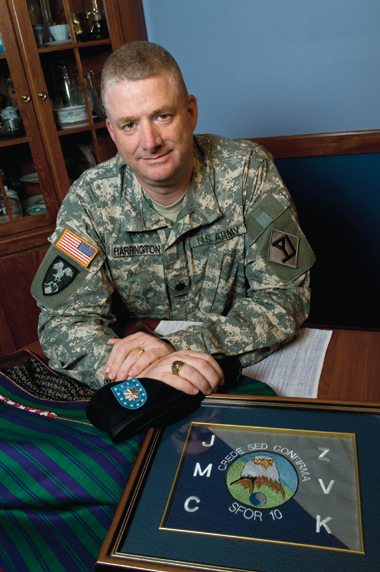 Harrington, an insurance executive and National Guard lieutenant colonel, in his Boston home. Before him at left is an Afghan robe, at right a plaque from his service in Bosnia. Photograph: Lee Pellegrini