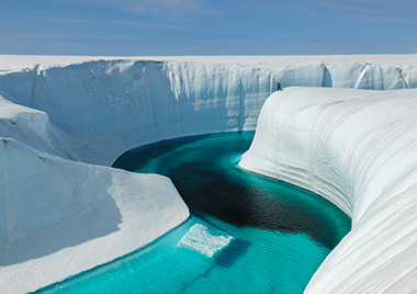 The 150-foot walls of Birthday Canyon on the Greenland Ice Sheet in June 2009. The black deposit at the bottom of the channel is cryoconite, a windborne dust containing rock particles and industrial soot that absorbs solar radiation. Photograph: James Balog / Extreme Ice Survey. Click on image to enlarge.