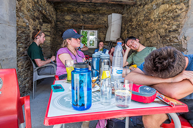 Around table in foreground, from left, Muir, Holterman, and Street after hiking 19 miles and climbing 2,600 feet. Olander sits behind them at far left. Click image to enlarge.