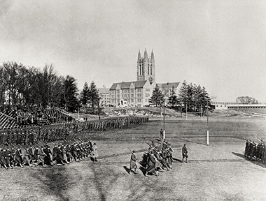 The Student Army Training Corps, a precursor to ROTC, drills on Alumni Field in 1918. In the distance are newly erected barracks. Image: John J. Burns Library. Click image to enlarge.