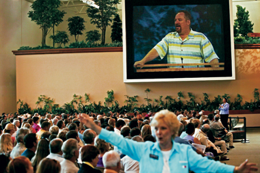 During a sermon at Saddleback Church, Lake Forest, California, Pastor Rick Warren is seen on the monitor. The woman in the foreground is an usher.