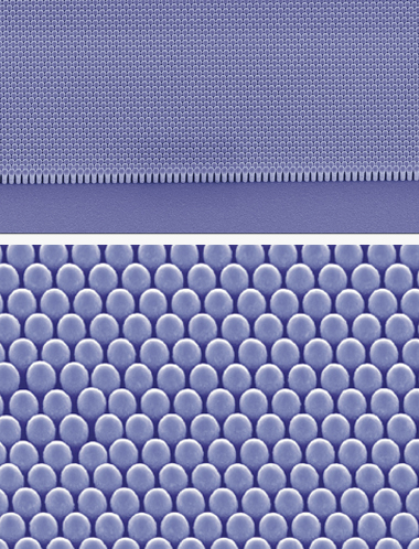 Electron microscope images of a complete nanocoax solar cell, at the edge of the cell array (top) and in a tilted close-up (bottom). Their true color, viewed with the eye, would be pitch black. Photographs: Jakub Rybczynski