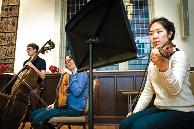 Violinist Annie Jihyo Park '13 (right) during a rehearsal of Cage's Concert for Piano and Orchestra. Photograph: J.D. Levine