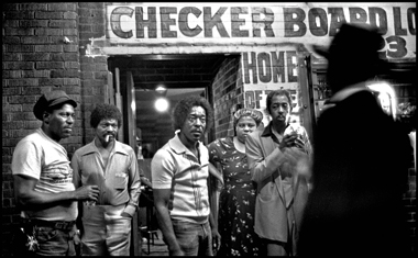Guy (striped shirt) and company outside the Checkerboard, 1982. Photograph: Marc PoKempner. Click image to enlarge.