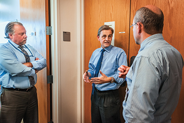 In a hallway conference with the Feinstein Institute's Christopher Czura, VP for scientific affairs (left), and Tom Coleman, director of technology transfer. Photograph: Gary Wayne Gilbert