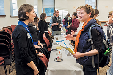High school theology teacher Amanda Vallimont, MTS'08 (left), talks with Grace Agolia, a first-year MTS student. Agolia holds a map of expo presenters. image: Lee Pellegrini